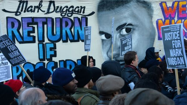 People stand beside a banner depicting Mark Duggan, who was shot dead by police, outside Tottenham Police Station in London on January 11, 2014, during a vigil following a jury verdict on January 8, 2014 ruling that Mark Duggan was lawfully killed when he was shot dead by police in August 2011.  - Sputnik International