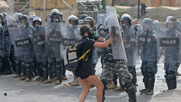 A Lebanese policeman hits a demonstrator during clashes in downtown Beirut on August 8, 2020, following a demonstration against a political leadership they blame for a monster explosion that killed more than 150 people and disfigured the capital Beirut. - Sputnik International