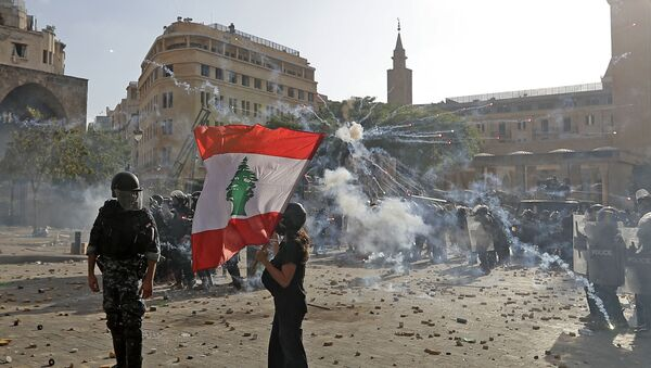 A Lebanese protester waves the national flag during clashes with security forces in downtown Beirut on August 8, 2020, following a demonstration against a political leadership they blame for a monster explosion that killed more than 150 people and disfigured the capital Beirut. - Sputnik International