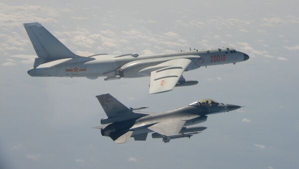 This handout photo taken and released on 10 February 2020 by Taiwan's Defence Ministry shows a Taiwanese F-16 fighter jet flying next to a Chinese H-6 bomber (top) in Taiwan's airspace. - Sputnik International
