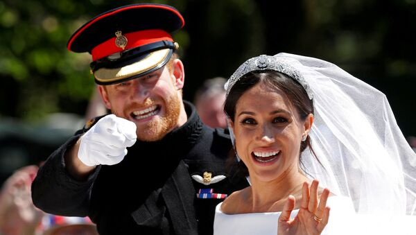 Britain's Prince Harry gestures next to his wife, Meghan, as they ride a horse-drawn carriage after their wedding ceremony at St George's Chapel in Windsor Castle in Windsor, Britain, May 19, 2018 - Sputnik International