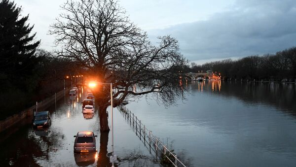 Cars are surrounded by water on a flooded road beside the River Thames in west London, Britain - Sputnik International