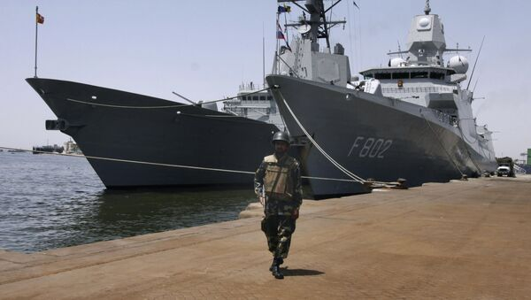 A Pakistani soldier stands guard next to the ships of Standing NATO Maritime Group One docked in Karachi, Pakistan, file photo. - Sputnik International