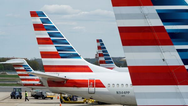 A member of a ground crew walks past American Airlines planes parked at the gate during the coronavirus disease (COVID-19) outbreak at Ronald Reagan National Airport in Washington, U.S., April 5, 2020.  - Sputnik International