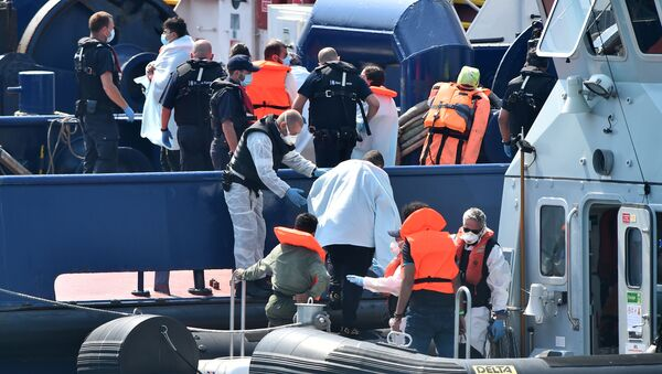 UK Border Force officers help migrants, believed to have been picked up from boats in the Channel, disembark from Coastal patrol vessel HMC Speedwell, in the port of Dover, on the south-east coast of England on 9 August 2020. (Photo by Glyn KIRK / AFP) - Sputnik International