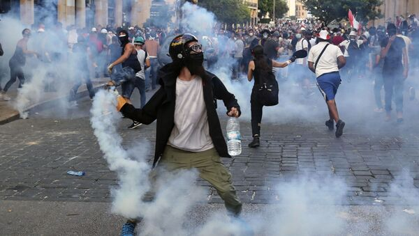 Protesters throw back tear gas canisters towards riot policemen during an anti-government protest, in the aftermath of last Tuesday's massive explosion which devastated Beirut, Lebanon, Monday, Aug. 10, 2020 - Sputnik International