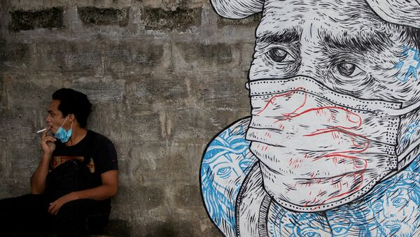 A man smokes a cigarette next to a mural of a man wearing a protective mask amid the coronavirus disease (COVID-19) outbreak in Quezon City, Metro Manila, Philippines, July 30, 2020.  - Sputnik International