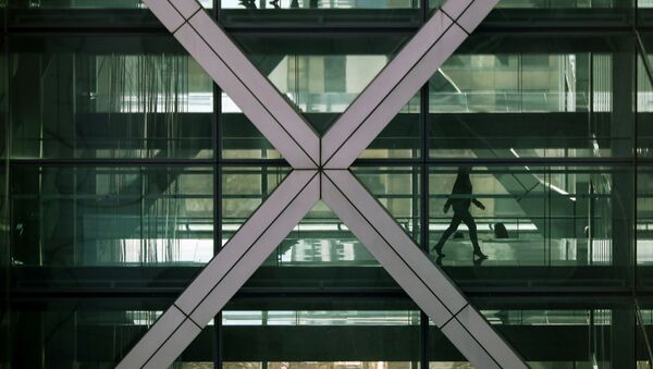 FILE PHOTO: People walk in an office in the financial centre of Canary Wharf in London, Britain March 6, 2020 - Sputnik International
