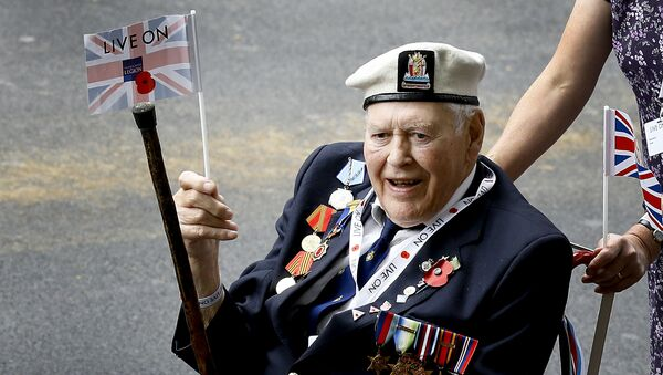A veteran waves a flag during the parade to commemorate VJ day, as it passes along Whitehall in London, Saturday, Aug. 15, 2015. The parade, comprised of veterans of the Far East Campaign, their families and descendants, led by Pipes and Drums drawn from the Army, was to mark the 70th anniversary of the victory over Japan during World War II. - Sputnik International