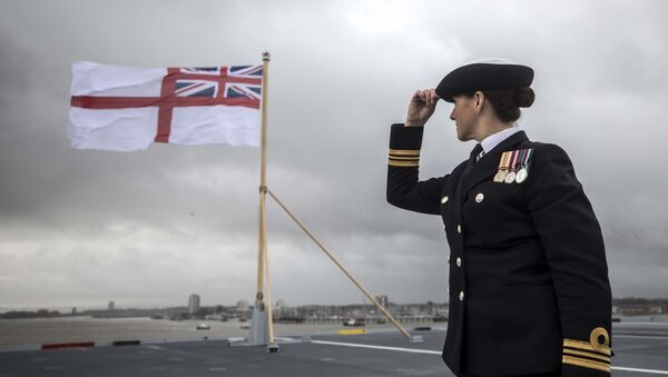 A naval officer looks up at the fluttering White ensign flag hoisted at the stern during the Commissioning Ceremony for the Royal Navy aircraft carrier HMS Queen Elizabeth at HM Naval Base in Portsmouth, southern England on December 7, 2017. - Sputnik International