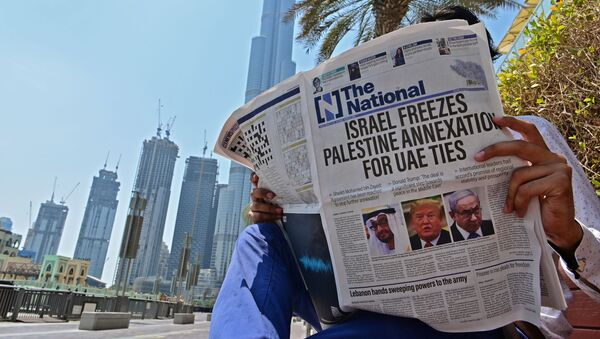 A man reads a copy of UAE-based The National newspaper near the Burj Khalifa, the tallest structure and building in the world since 2009, in the gulf emirate of Dubai on August 14, 2020, as the publication's headline reflects the previous day's news as Israel and the UAE agreed to normalise relations in a landmark US-brokered deal. - The deal marks only the third such accord the Jewish state has struck with an Arab nation, an historic shift making the Gulf state only the third Arab country to establish full diplomatic ties with the Jewish state. The Palestinian leadership voiced its strong rejection and condemnation of the deal and announced it would withdraw its envoy from the UAE, and Turkey also condemned the deal as an act of treachery. - Sputnik International