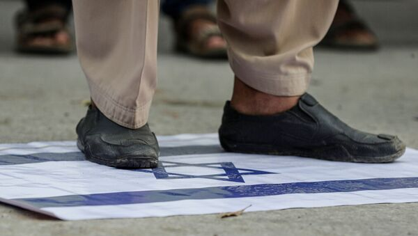 A supporter of religious and political party Jamaat-e-Islami (JI) steps on an Israeli flag to condemn the diplomatic agreement between the United Arab Emirates (UAE) and Israel, during a protest in Karachi, Pakistan August 16, 2020. - Sputnik International
