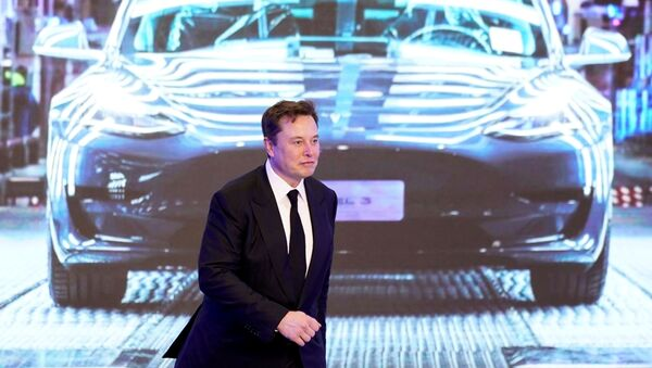 Tesla Inc CEO Elon Musk walks next to a screen showing an image of Tesla Model 3 car during an opening ceremony for Tesla China-made Model Y program in Shanghai, China January 7, 2020 - Sputnik International