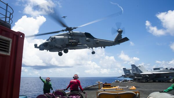"""An MH-60R Seahawk assigned to the """"Saberhawks"""" of Helicopter Maritime Strike Squadron (HSM) 77 lifts off the flight deck of America's only forward-deployed aircraft carrier USS Ronald Reagan (CVN 76)  while conducting operations in the South China Sea. - Sputnik International"""
