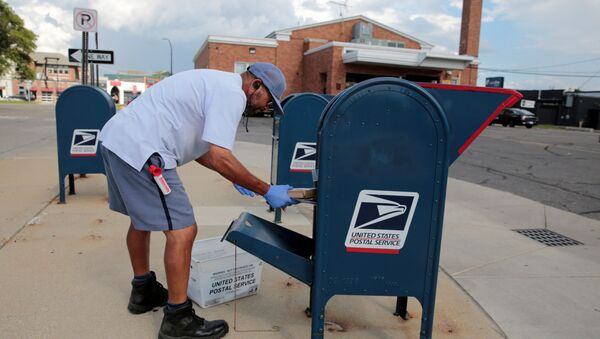 A United States Postal Service (USPS) worker handles the mail in a drop-off box behind a post office in Oak Park, Michigan, U.S.  August 17, 2020 - Sputnik International