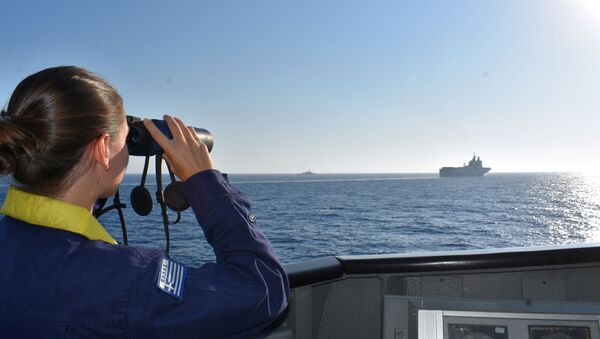 A woman looks through binoculars as Greek and French vessels sail in formation during a joint military exercise in Mediterranean sea, in this undated handout image obtained by Reuters on August 13, 2020 - Sputnik International