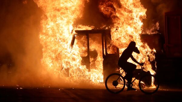 A man on a bike rides past a city truck on fire outside the Kenosha County Courthouse in Kenosha, Wisconsin, U.S., during protests following the police shooting of Black man Jacob Blake August 23, 2020. - Sputnik International