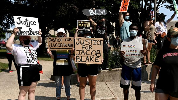 People hold placards as they gather for a protest outside the Kenosha County Courthouse after a Black man, identified as Jacob Blake, was shot several times by police last night in Kenosha, Wisconsin, U.S. August 24, 2020. Picture taken August 24, 2020 - Sputnik International