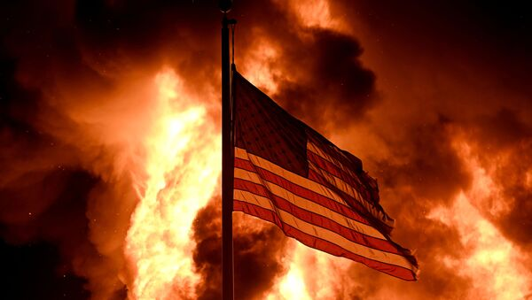 Flames engulf the Community Corrections Division building as an American flag flutters on a pole in an arson attack after a black man identified as Jacob Blake, was shot several times by police in Kenosha, Wisconsin, 24 August 2020.  - Sputnik International