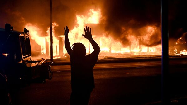 A man walks by an armoured vehicle as B&L Office Furniture burns in the background as protests turn to fires after a Black man, identified as Jacob Blake, was shot several times by police last night in Kenosha, Wisconsin, U.S. August 24, 2020 - Sputnik International