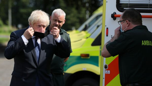 Britain's Prime Minister Boris Johnson puts on a mask at the Northern Ireland Ambulance Service HQ during his visit to Belfast, Northern Ireland August 13, 2020 - Sputnik International