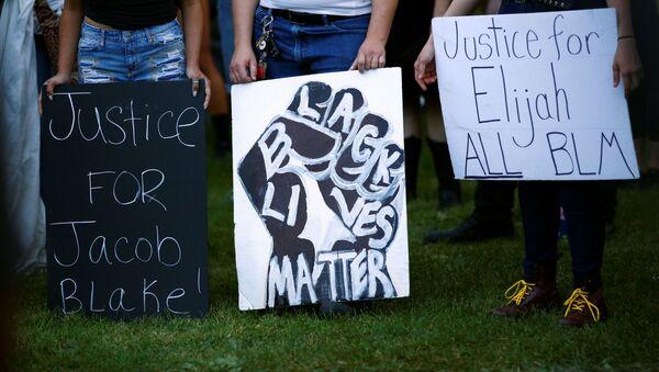Protesters hold signs calling for justice for Jacob Blake and Elijah McClain at a demonstration against police violence in Denver, Colorado, U.S., August 24, 2020. - Sputnik International