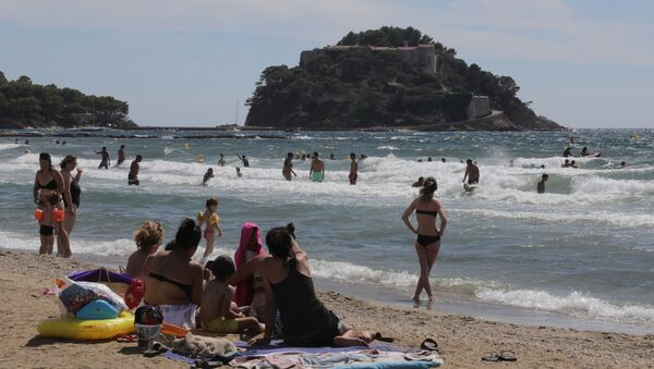 People sunbathe on the beach of Bregancon fort, the French presidential summer residence, where French President Emmanuel Macron stays for holidays in Bormes-les-Mimosas, August 17, 2020 - Sputnik International