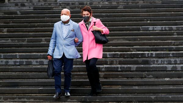 A couple wearing protective face masks walk down the stairs amid the coronavirus disease (COVID-19) outbreak in Brussels, Belgium August 25, 2020. Picture taken August 25, 2020. - Sputnik International
