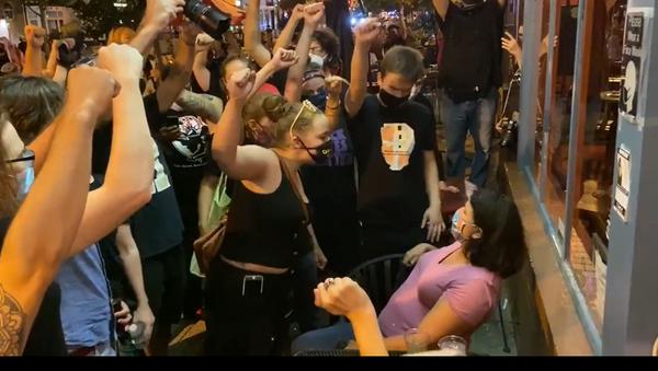 A screenshot from a video showing BLM protestors confronting diners outside a DC restaurant - Sputnik International