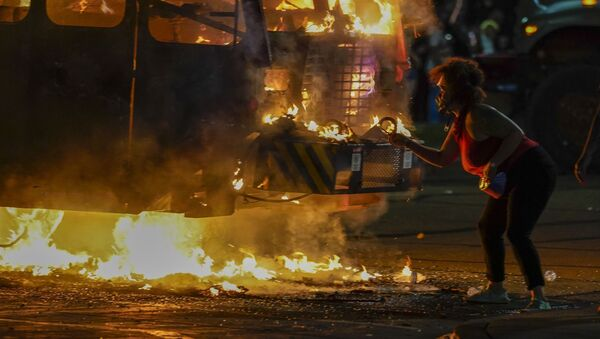 A protester lights a cigarette on a garbage truck that was set on fire during protests late Monday, Aug. 24, 2020, in Kenosha, Wis., sparked by the shooting of Jacob Blake by a Kenosha Police officer a day earlier.  - Sputnik International
