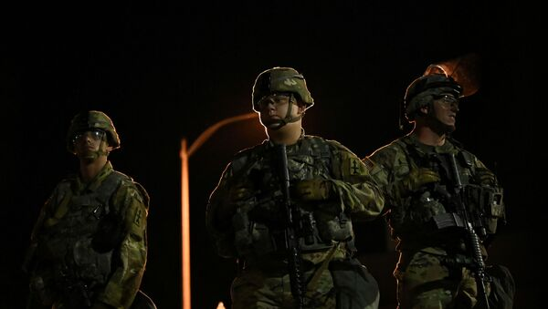 Members of the Wisconsin National Guard keep watch at their post behind the Kenosha Police Department building following the police shooting of Jacob Blake, a Black man, in Kenosha, Wisconsin, U.S., August 27, 2020. - Sputnik International