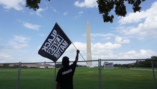 A participant of the rally commemorating the 57th anniversary of the March on Washington is seen holding a Black Lives Matter flag in front of the Washington Monument. - Sputnik International