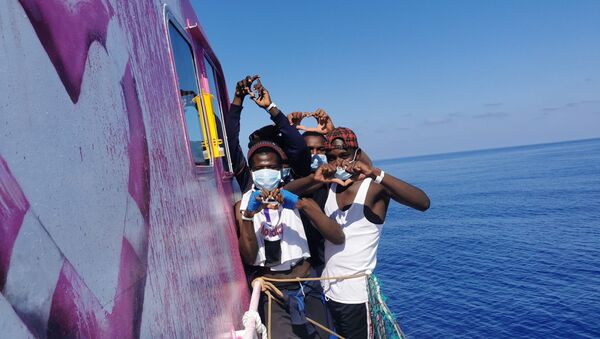 In this undated handout photo people pose for a photo after being rescued by the Louise Michel, a migrants search and rescue ship operating in the Mediterranean and financed by British street artist Banksy, at sea. - Sputnik International