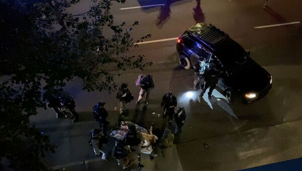 SENSITIVE MATERIAL. THIS IMAGE MAY OFFEND OR DISTURB    Medics and police personnel surround the victim of a shooting in Portland, Oregon, U.S. August 29, 2020, in this still image obtained from a social media video. Courtesy of Sergio Olmos/Social Media via REUTERS. ATTENTION EDITORS - THIS IMAGE HAS BEEN SUPPLIED BY A THIRD PARTY. MANDATORY CREDIT SERGIO OLMOS. NO RESALES. NO ARCHIVES. - Sputnik International