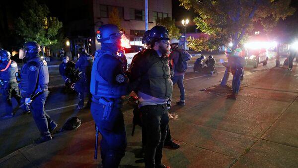 Police officers detain a demonstrator during a protest against police violence and racial injustice in Portland, Oregon, U.S., August 24, 2020.   - Sputnik International