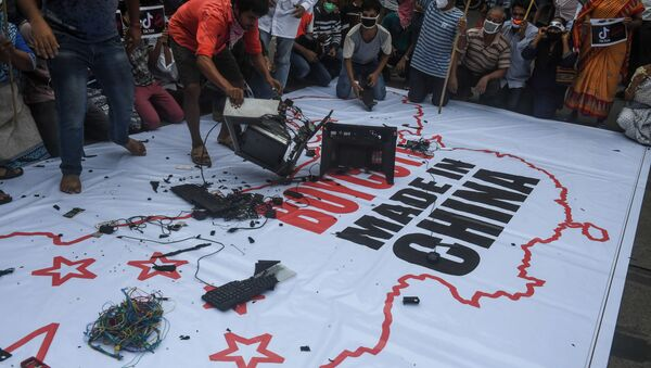 Congress party supporters leave Chinese goods on a flag displaying the country and flag of China along with an inscription reading 'Boycott Made in China' before burning them during an anti-China demonstration in Kolkata on Juane 18, 2020 - Sputnik International