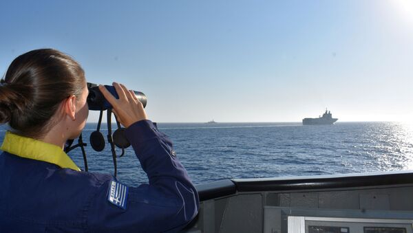 A woman looks through binoculars as Greek and French vessels sail in formation during a joint military exercise in Mediterranean sea, in this undated handout image - Sputnik International