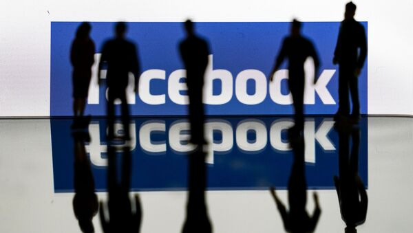 (FILES) In this file photo taken on February 14, 2020 silhouettes are seen in front of the logo of US social media Facebook in Brussels - Sputnik International