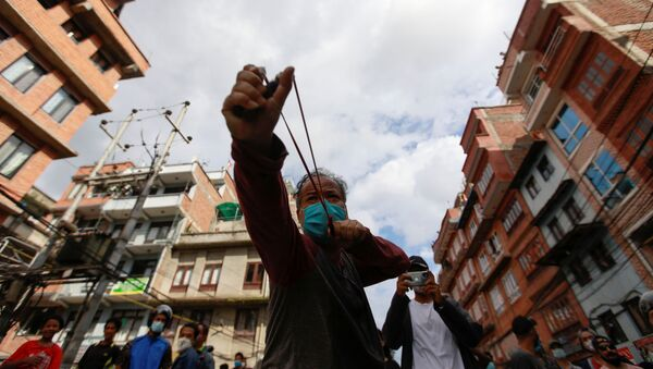 A man uses a slingshot during the protest after locals try to pull the chariot of Rato Machhindranath amid the ban on public and religious gatherings to control the spread of the coronavirus disease (COVID-19) in Lalitpur, Nepal September 3, 2020 - Sputnik International