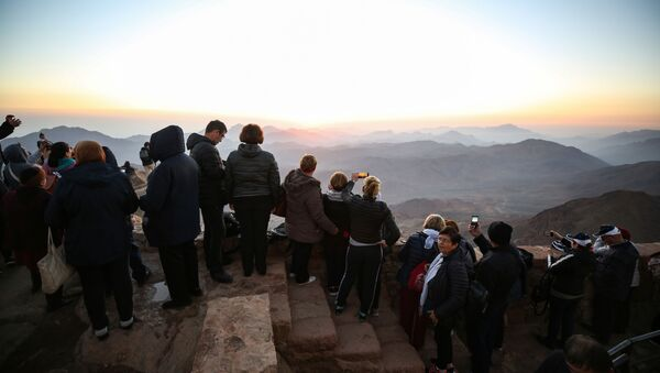 Tourists stand to watch the sunrise after scaling Mount Catherine, above the 6th-century Greek Orthodox Christian monastery of Saint Catherine, near the Egyptian town of the same name in south of the Sinai peninsula, on October 19, 2018, as part of an inter-religious peace conference under slogan Here We pray together.  - Sputnik International