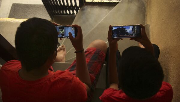 Indian children play online game PUBG on their mobile phones sitting on stairs outside their house  in Hyderabad, India, Friday, April 5, 2019.  - Sputnik International