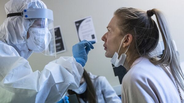 A medical worker, left, performs a COVID-19 test at a test center at Vnukovo airport outside Moscow, Russia, Friday, Aug. 7, 2020. Authorities in Russia say they are about to approve a COVID-19 vaccine, with mass vaccinations planned as early as October 2020, using shots that are yet to complete clinical trials - Sputnik International