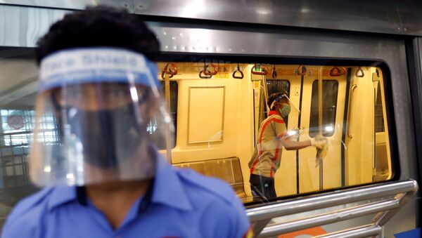 A worker wearing a face shield and mask cleans inside a train at a Delhi Metro station ahead of the restart of its operations, amidst the spread of coronavirus disease (COVID-19), in New Delhi, India, September 3, 2020. - Sputnik International