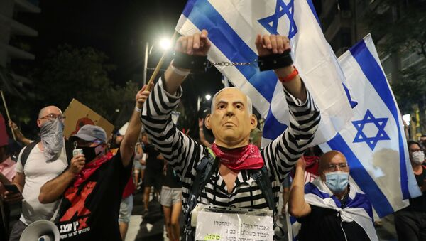 A protester wearing a mask depicting Israeli Prime Minister Benjamin Netanyahu attends a demonstration against the PM's alleged corruption and economic hardship stemming from lockdown during the coronavirus disease (COVID-19) crisis, near his residence in Jerusalem August 29, 2020 - Sputnik International