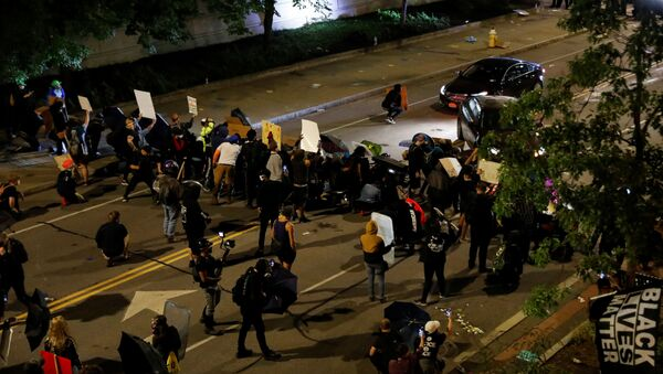 Demonstrators take cover as cars pass during a protest over the death of a Black man, Daniel Prude, after police put a spit hood over his head during an arrest on March 23, in Rochester, New York, U.S. September 4, 2020 - Sputnik International