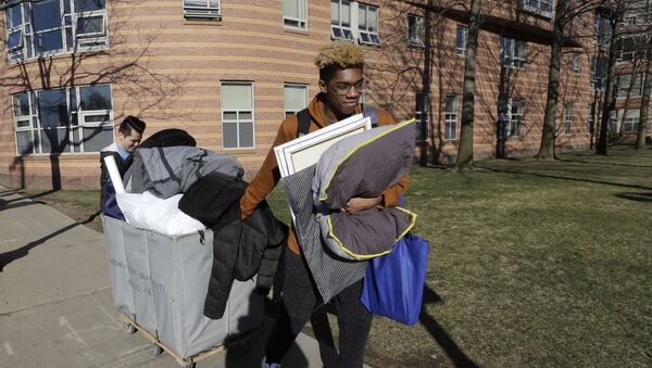 Northeastern University sophomore Philip Thomas, of Hamden, Conn., front, pulls a cart of belongings as he moves out of his residence hall as classmate Jarrett Anderson, of Las Vegas, left, assists him, Sunday, March 15, 2020, in Boston. Students have been asked by the school to move out of residence halls out of concern about the spread of the coronavirus. For most people, the new coronavirus causes only mild or moderate symptoms, such as fever and cough. For some, especially older adults and people with existing health problems, it can cause more severe illness, including pneumonia. The vast majority of people recover from the new virus. - Sputnik International