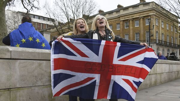 Brexit supporters hold the Union Jack with a text reading Goodbye EU as they celebrate next to a person wearing the EU flag in London, Friday, Jan. 31, 2020 - Sputnik International