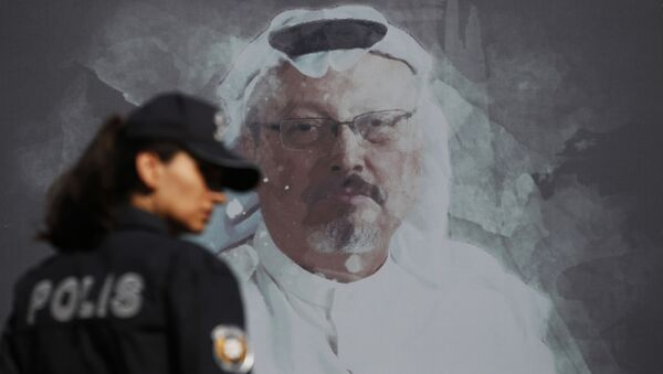 A Turkish police officer walks past a picture of slain Saudi journalist Jamal Khashoggi prior to a ceremony, near the Saudi Arabia consulate in Istanbul, marking the one-year anniversary of his death, Wednesday, Oct. 2, 2019 - Sputnik International