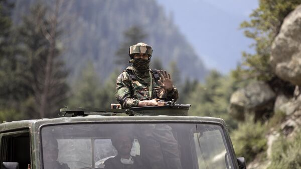 An Indian army soldier keeps guard on top of his vehicle as their convoy moves on the Srinagar- Ladakh highway at Gagangeer, north-east of Srinagar, Indian-controlled Kashmir on Tuesday, 1 September 2020. - Sputnik International