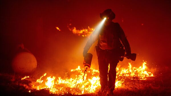 Firefighters cut defensive lines and light backfires to protect structures behind a CalFire fire station during the Bear fire, part of the North Lightning Complex fires in the Berry Creek area of unincorporated Butte County, California on September 9, 2020 - Sputnik International